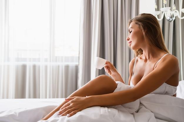 Belle femme en soutien-gorge blanc s'asseoir dans un lit de luxe à la lumière du matin depuis la fenêtre, tenir une petite tasse de boisson pour le petit-déjeuner, modèle sexy à l'intérieur