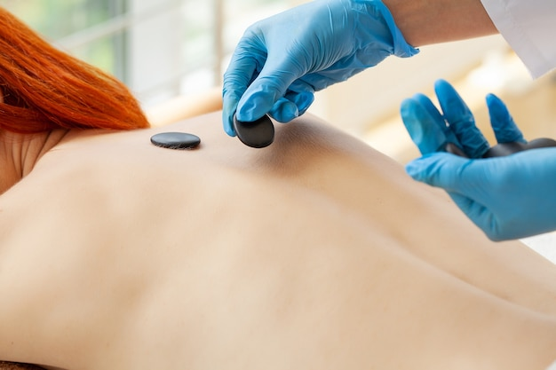 Belle femme spa soins de beauté de massage aux pierres chaudes.