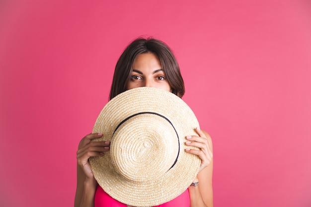 Belle femme sportive bronzée en bikini et chapeau de paille sur rose