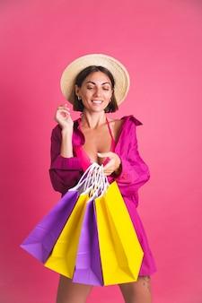 Belle femme sportive bronzée en chemise et bikini avec des sacs colorés heureux excité sur rose