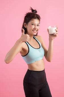 Belle femme sportive buvant du lait