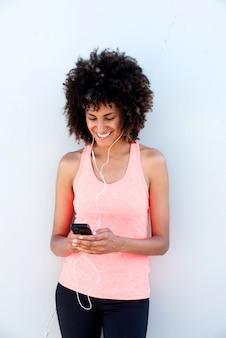 Belle femme sportive avec un casque tenant un téléphone mobile