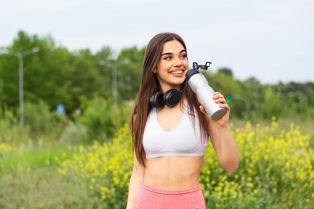 Belle femme sportive eau potable tout en se reposant de l'exercice.