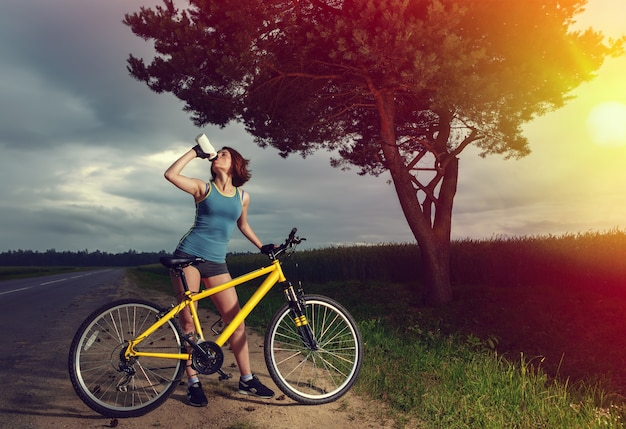 Belle femme sportive avec de l'eau potable à vélo à partir d'une bouteille.