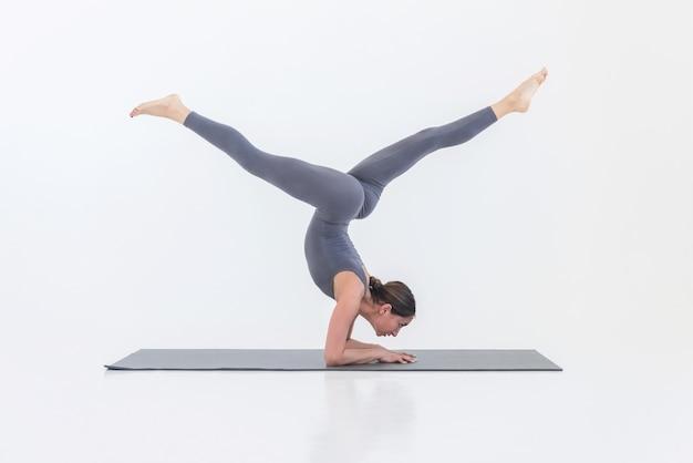 Belle femme sportive faisant du yoga sur le tapis sur fond blanc. concept de sport et de santé