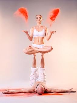 Belle femme sportive homme en vêtements blancs faisant des asanas de yoga avec du sable coloré à l'intérieur