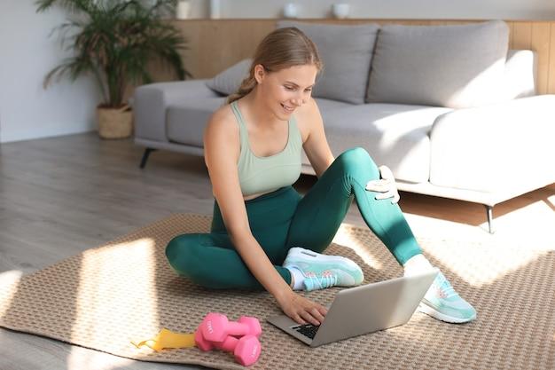 Belle femme sportive mince en tenue de sport est assise sur le sol avec des haltères et utilise un ordinateur portable à la maison dans le salon. mode de vie sain. restez à la maison activités.