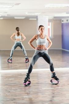 Belle femme sportive posant avec des chaussures de sauts kangoo dans la salle de gym