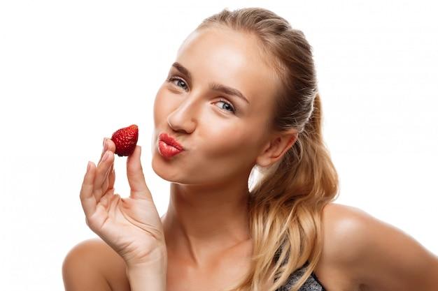 Belle femme sportive posant, mangeant des fraises