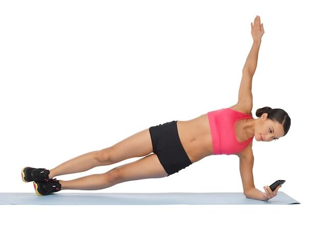 Belle femme sportive avec smartphone faisant de l'exercice