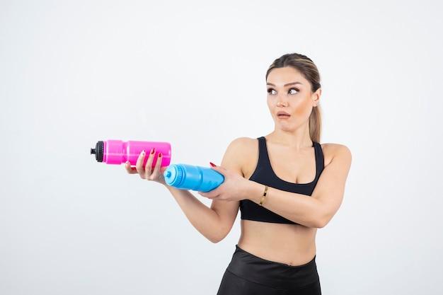 Belle femme sportive tenant des bouteilles avec de l'eau sur blanc