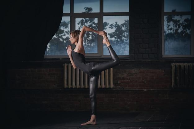 Belle femme sportive yogi fit pratiquer le yoga asana natarajasana - lord of the dance pose dans le hall sombre
