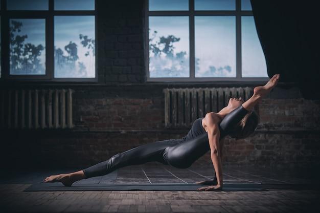 Belle femme sportive yogini fit pratique le yoga asana eka pada ardha purvottanasana dans le hall sombre