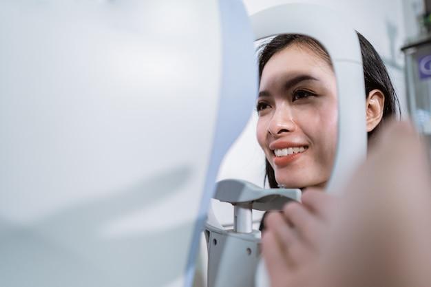 Une belle femme subit un examen à l'aide d'un examinateur oculaire dans la salle de la clinique ophtalmologique