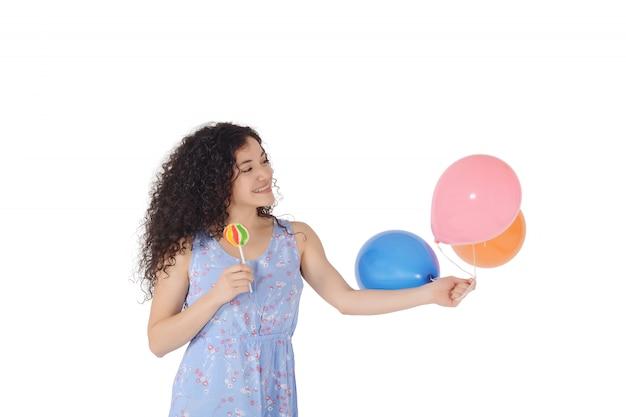 Belle femme avec sucette sucrée et ballons.