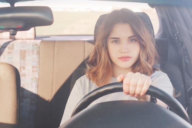 Belle femme sûre d'elle dans les transports conduit la voiture