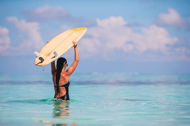 Belle femme surfeuse prête à surfer dans la mer turquoise sur stand up paddle board en vacances exotiques
