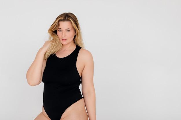 Belle femme en surpoids en maillot de bain noir sur mur blanc
