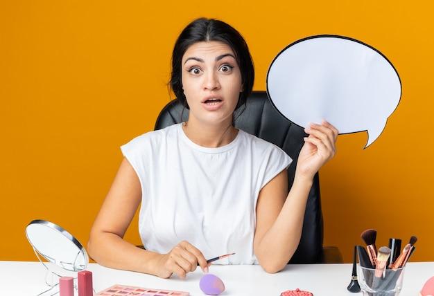 Une belle femme surprise est assise à table avec des outils de maquillage tenant une bulle de dialogue avec un pinceau de maquillage