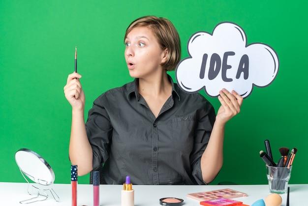 Une belle femme surprise est assise à table avec des outils de maquillage tenant une bulle d'idée avec un pinceau de maquillage