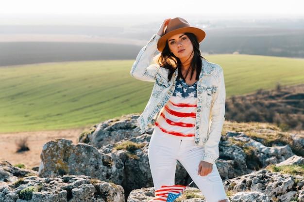 Belle femme en t-shirt drapeau américain posant au sommet de la montagne