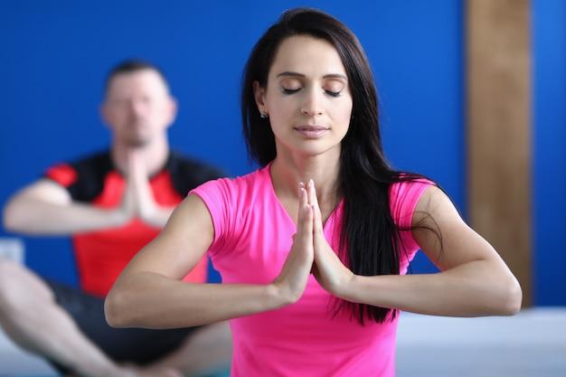Belle femme en t-shirt rose s'asseoir sur un tapis dans le hall avec les yeux fermés et pratiquer le yoga