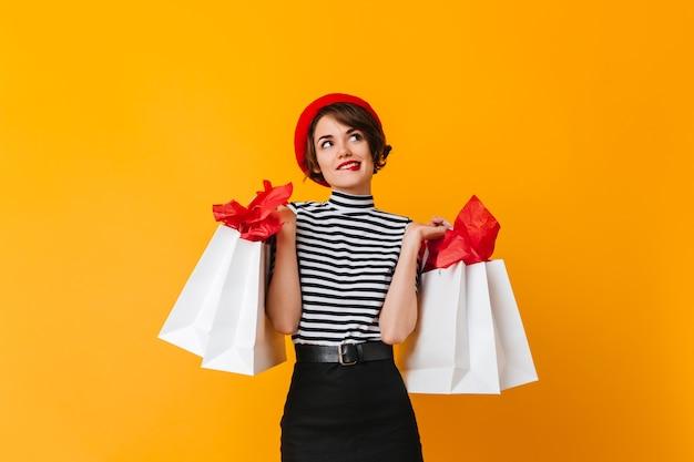 Belle femme en t-shirt stipulé et béret rouge tenant des sacs de magasin
