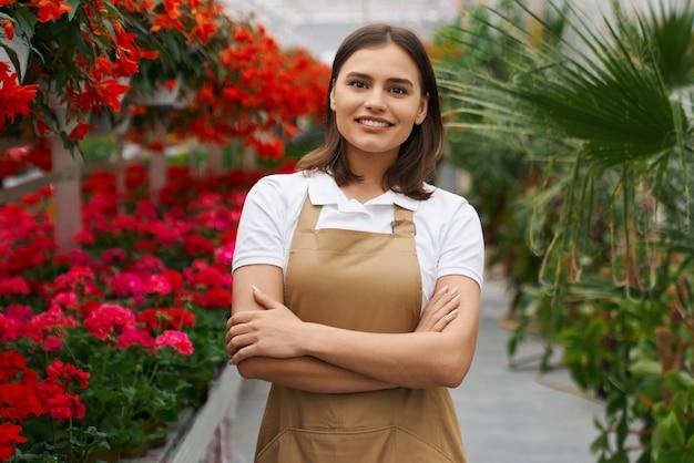 Belle femme en tablier posant parmi les fleurs à l'orangerie