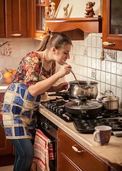 Belle femme en tablier en remuant la soupe avec une cuillère de cuisine