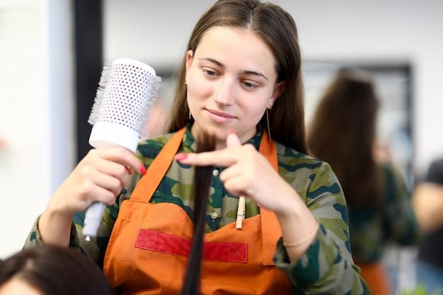 Belle femme en tablier tenir longue mèche de gros plan de cheveux et peigne
