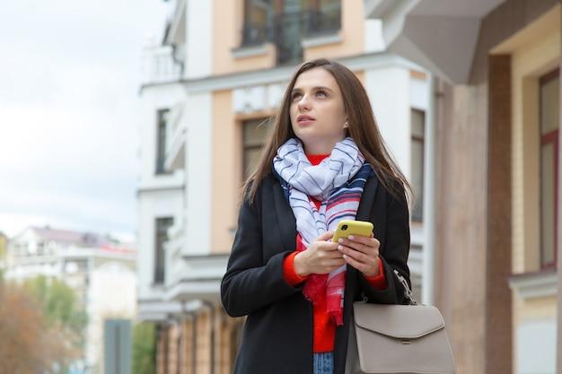 Belle femme en tapant un téléphone mobile dans la ville