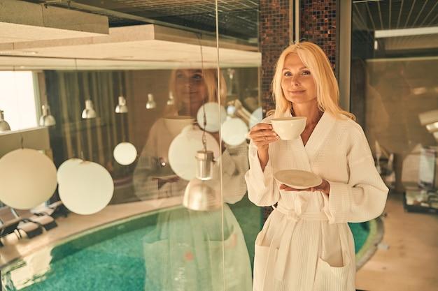 Belle femme avec une tasse de café à la main tout en posant devant la caméra dans un hôtel de villégiature