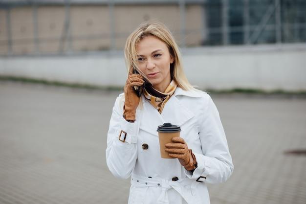 Belle femme avec une tasse de café près de l'immeuble de bureaux.