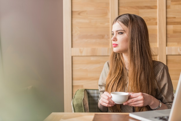 Belle femme avec une tasse de thé à la recherche du côté