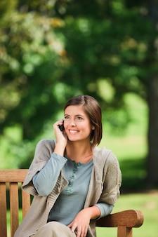 Belle femme téléphonant sur le banc