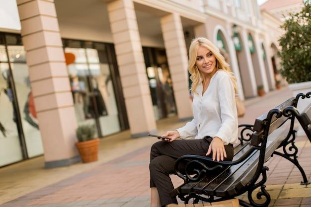 Belle femme avec un téléphone portable assis sur le banc