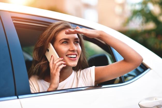 Belle femme avec téléphone souriant alors qu'il était assis sur la banquette arrière de la voiture.