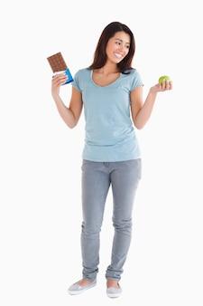 Belle femme tenant une barre de chocolat et une pomme