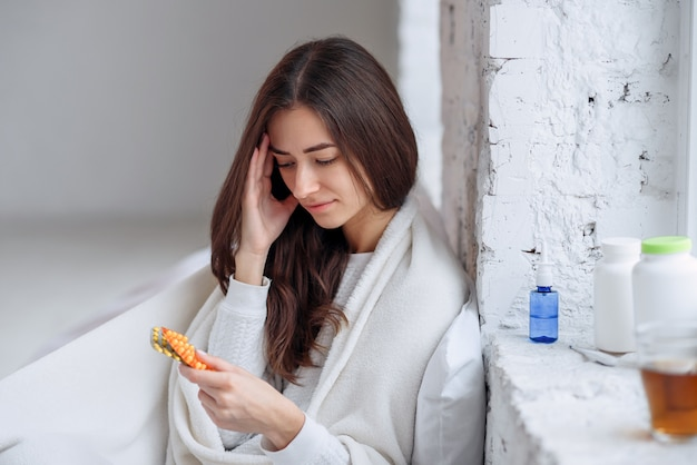 Belle femme tenant un blister avec des pilules à la main