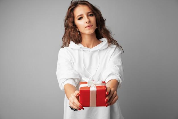 Belle femme tenant une boîte cadeau rouge dans ses mains