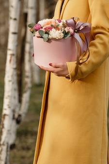 Belle femme tenant une boîte rose avec des fleurs. cadeau à la fête des femmes.