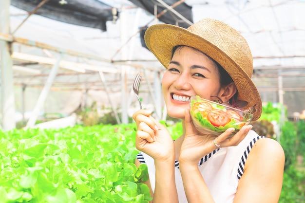 Belle femme tenant un bol de salade dans une ferme biologique. mode de vie sain