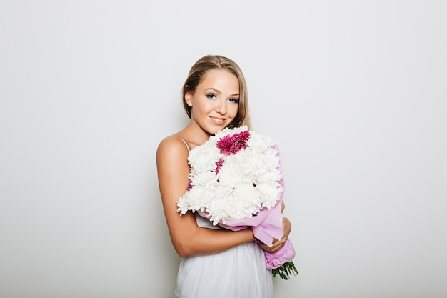 Belle femme tenant un bouquet de fleurs