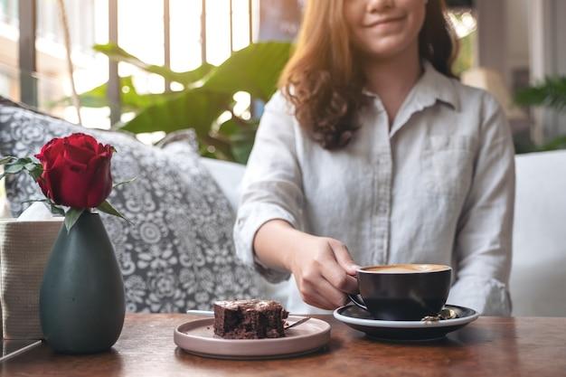Belle femme tenant et buvant du café latte chaud avec un gâteau brownie sur la table au café