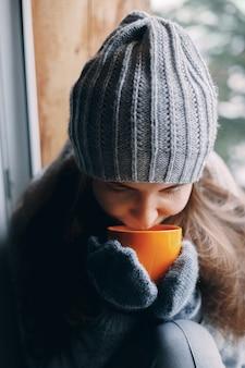 Belle femme tenant et buvant une tasse de café