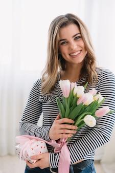 Belle femme tenant cadeau et printemps bouquet de tulipes dans ses mains.