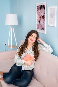 Belle femme tenant un cahier sur le canapé