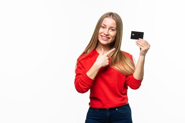 Belle femme tenant une carte de crédit vide et la pointant du doigt, isolée sur une surface blanche