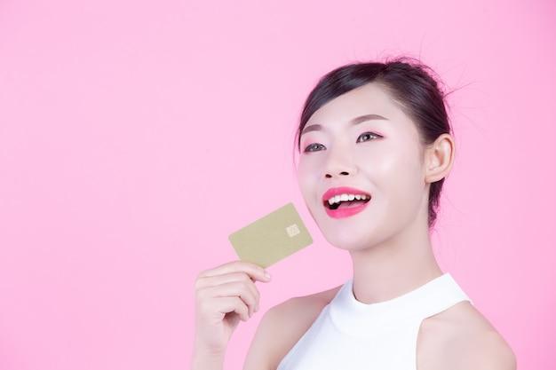 Belle femme tenant une carte sur un fond rose.