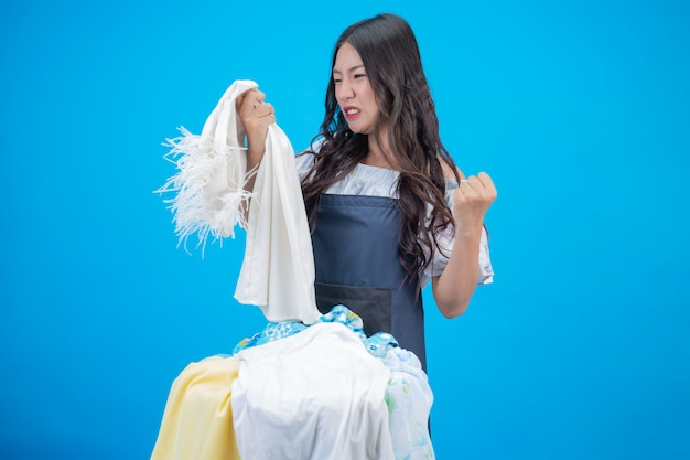 Une belle femme tenant un chiffon prêt à laver sur bleu